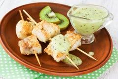 Ψάρια kebabs στα ξύλινα οβελίδια με τη σάλτσα ακτινίδιων φρούτων Στοκ Φωτογραφίες