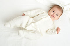 Ψέμα μωρών portait πετσέτα στο κρεβάτι, κίτρινος που τονίζεται στην άσπρη Στοκ Φωτογραφίες