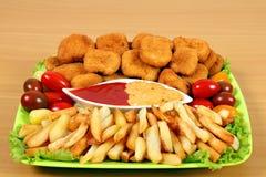 Ψήγματα και τηγανιτές πατάτες κοτόπουλου στο πιάτο στοκ φωτογραφία
