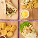 Ψήγματα και τηγανιτές πατάτες, shawarma, ελληνικά γυροσκόπια και pita με τη σοκολάτα και ακτινίδιο στους πίνακες σε έναν πίνακα Στοκ εικόνα με δικαίωμα ελεύθερης χρήσης