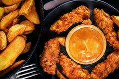 Ψήγματα κοτόπουλου, τηγανισμένες πατάτες και σάλτσα σε ένα μαύρο υπόβαθρο Στοκ φωτογραφίες με δικαίωμα ελεύθερης χρήσης