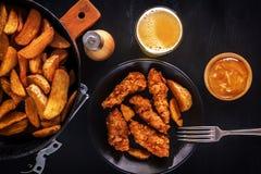 Ψήγματα κοτόπουλου, τηγανισμένες πατάτες, μπύρα και σάλτσα Στοκ Φωτογραφία