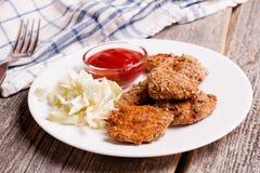 Ψήγματα κοτόπουλου με τη σάλτσα tomate και λαχανικά στον ξύλινο πίνακα Στοκ εικόνες με δικαίωμα ελεύθερης χρήσης