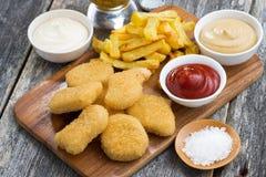 Ψήγματα κοτόπουλου με τις τηγανιτές πατάτες και τις διαφορετικές σάλτσες Στοκ Εικόνες