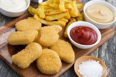 Ψήγματα κοτόπουλου με τις τηγανιτές πατάτες και τις διαφορετικές σάλτσες Στοκ εικόνες με δικαίωμα ελεύθερης χρήσης