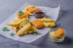 Ψήγματα κοτόπουλου με το κέτσαπ και τη σάλτσα, στο υπόβαθρο πετρών Εκλεκτική εστίαση Στοκ Φωτογραφίες