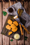 Ψήγματα κοτόπουλου στον ξύλινο τέμνοντα πίνακα με το κέτσαπ και τη σάλτσα, στο ξύλινο υπόβαθρο Εκλεκτική εστίαση Τοπ όψη Στοκ εικόνες με δικαίωμα ελεύθερης χρήσης