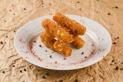 Ψήγματα τυριών στο πιάτο στο υπόβαθρο εγγράφου τεχνών στοκ φωτογραφία