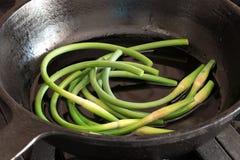 Ψήνοντας βέλη του σκόρδου στο τηγανίζοντας τηγάνι χυτοσιδήρου Στοκ φωτογραφία με δικαίωμα ελεύθερης χρήσης