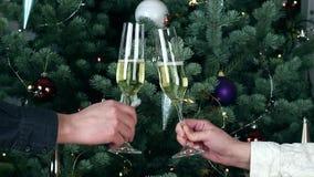 Ψήνοντας γυαλιά ζεύγους με το άσπρο κρασί σαμπάνιας από το διακοσμημένο φωτισμένο χριστουγεννιάτικο δέντρο απόθεμα βίντεο