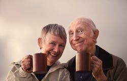 Ψήσιμο ζεύγους χαμόγελου ανώτερο με τις κούπες Στοκ εικόνα με δικαίωμα ελεύθερης χρήσης