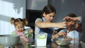 Ψήσιμο μαγείρων τριών το όμορφο παιδιών στην κουζίνα, σπάζει το αυγό στο αλεύρι, χύνει το νερό και ζυμώνει τη ζύμη απόθεμα βίντεο