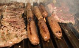 Ψήσιμο στη σχάρα των λουκάνικων και της μπριζόλας βόειου κρέατος Στοκ Εικόνα
