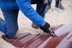 Ψαλίδι χρήσης εργαζομένων για την κοπή του φύλλου υλικού κατασκευής σκεπής μετάλλων στοκ εικόνες