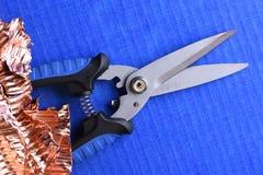 Ψαλιδίστε το απόρριμα κοπτών και χαλκού στο μπλε υπόβαθρο στοκ φωτογραφία με δικαίωμα ελεύθερης χρήσης