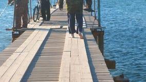 Ψαράδες με την αλιεία των ράβδων σε μια ξύλινη πόλη θάλασσας αποβαθρών παράκτια απόθεμα βίντεο