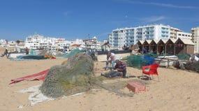 Ψαράδες που επιδιορθώνουν τα δίχτυα τους Στη μακριά, ευρεία, λεπτή αμμώδη παραλία ψαράδων Armacao de Pera, Αλγκάρβε, Πορτογαλία Στοκ εικόνα με δικαίωμα ελεύθερης χρήσης