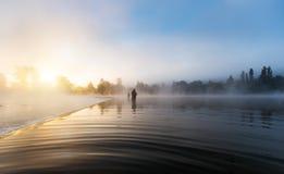 Ψαράδες που κρατούν τη ράβδο αλιείας, που στέκεται στον ποταμό στοκ εικόνα