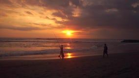 Ψαράς και γιος στην παραλία στο ηλιοβασίλεμα απόθεμα βίντεο