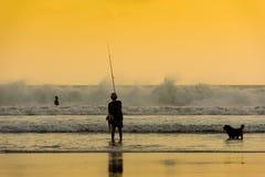 Ψαράς και σκυλί, παραλία Kuta, Μπαλί στοκ εικόνες