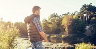Ψαράς με μια περιστροφή και ένα δόλωμα που πιάνουν τα ψάρια σε μια λίμνη ή έναν ποταμό Άτομο σε ένα Σαββατοκύριακο με έναν δρόμο  στοκ εικόνα