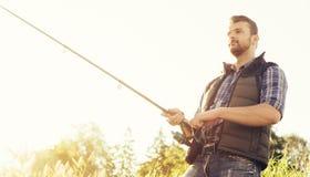 Ψαράς με μια περιστροφή και ένα δόλωμα που πιάνουν τα ψάρια σε μια λίμνη ή έναν ποταμό Άτομο σε ένα Σαββατοκύριακο με έναν δρόμο  στοκ εικόνες