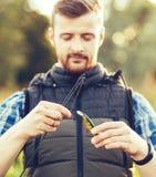 Ψαράς με μια περιστροφή και ένα δόλωμα που πιάνουν τα ψάρια σε μια λίμνη ή έναν ποταμό Άτομο σε ένα Σαββατοκύριακο με έναν δρόμο  στοκ φωτογραφίες με δικαίωμα ελεύθερης χρήσης
