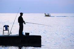 Ψαράς με μια ράβδο στο ηλιοβασίλεμα στοκ εικόνα με δικαίωμα ελεύθερης χρήσης