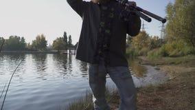 Ψαράς με τη μακριά γενειάδα stends στην όχθη ποταμού με την αλιεία των ράβδων Το άτομο εξετάζει την απόσταση, που καλύπτει τα μάτ φιλμ μικρού μήκους