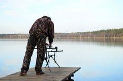 Ψαράς με το λοβό ράβδων, τροφοδότες, ηλεκτρονικοί συναγερμοί δαγκωμάτων στην αποβάθρα Στοκ Εικόνες