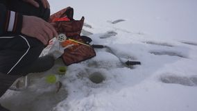 Ψαράς που αλιεύει στην τρύπα πάγου στη χειμερινή λίμνη Καλή σύλληψη στη χειμερινή αλιεία φιλμ μικρού μήκους