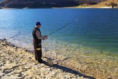 Ψαράς που αλιεύει στην μπλε λίμνη στοκ εικόνες