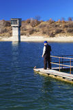 Ψαράς που αλιεύει στην μπλε λίμνη στοκ εικόνα