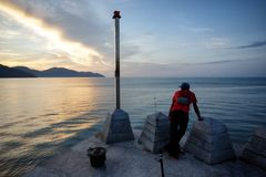 Ψαράς που παίρνει ένα σπάσιμο σε Batu Ferringhi στοκ εικόνα