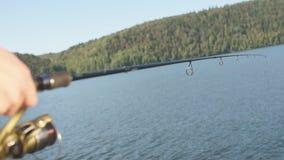 Ψαράς που προσπαθεί να πιάσει τα ψάρια στη λίμνη με τη ράβδο απόθεμα βίντεο