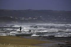 Ψαράς που στέκεται στο σπάσιμο ακτών με την αλιεία της ράβδου Στοκ εικόνα με δικαίωμα ελεύθερης χρήσης