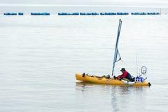 Ψαράς σε μια βάρκα που προσπαθεί να πιάσει ένα ψάρι χρησιμοποιώντας τον πόλο ψαριών Στοκ φωτογραφίες με δικαίωμα ελεύθερης χρήσης