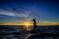 Ψαράς σκιαγραφιών που το δίχτυ στη λίμνη στο ηλιοβασίλεμα, Στοκ φωτογραφίες με δικαίωμα ελεύθερης χρήσης