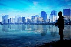 Ψαράς σκιαγραφιών στην ακτή και η πόλη στο υπόβαθρο Στοκ φωτογραφίες με δικαίωμα ελεύθερης χρήσης