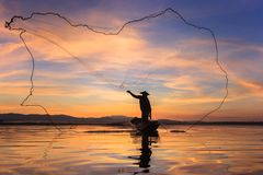 Ψαράς σκιαγραφιών στο αλιευτικό σκάφος που θέτει καθαρό με την ανατολή Στοκ Φωτογραφίες