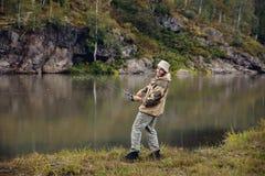 Ψαράς στα ψάρια συλλήψεων ποταμών στοκ εικόνες