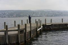Ψαράς στην αποβάθρα το χειμώνα μια βροχερή ημέρα στοκ εικόνες