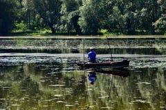 Ψαράς στη βάρκα στη λίμνη Στοκ Εικόνες