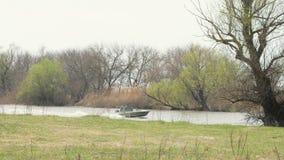 Ψαράς στη βάρκα μηχανών που πλέει με το νερό στα δέντρα υποβάθρου στην ακτή ποταμών φιλμ μικρού μήκους