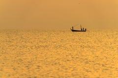 Ψαράς στη βάρκα πέρα από το δραματικό ηλιοβασίλεμα Στοκ φωτογραφία με δικαίωμα ελεύθερης χρήσης