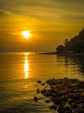 Ψαράς στη χρυσή θάλασσα στο ηλιοβασίλεμα Στοκ Φωτογραφίες