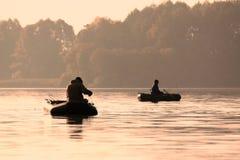 Ψαράδες σε μια βάρκα που πιάνει τα ψάρια νωρίς το πρωί Στοκ Εικόνα