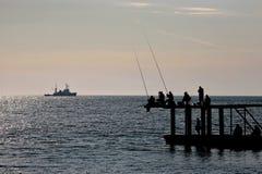 ψαράδες ψαριών σύλληψης που αλιεύουν αναπτύσσοντας έξω τις ράβδους καλάμων λιμνών που κολλούν τρία Στοκ φωτογραφία με δικαίωμα ελεύθερης χρήσης