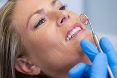 Ψαρευμένος εκμετάλλευση καθρέφτης οδοντιάτρων από τη γυναίκα στην ιατρική κλινική Στοκ Εικόνες