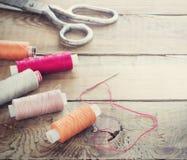 Ψαλίδι, μασούρια με το νήμα και βελόνες Παλαιά ράβοντας εργαλεία στο παλαιό ξύλινο υπόβαθρο γεωμετρικός παλαιός τρύγος εγγράφου δ Στοκ εικόνα με δικαίωμα ελεύθερης χρήσης